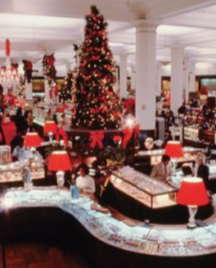 "<img src= ""department store.jpg"" alt= ""massive Christmas tree in the middle of the first floor of a department store with lamps with red shades on the counters zig zagging the selling floor"">"